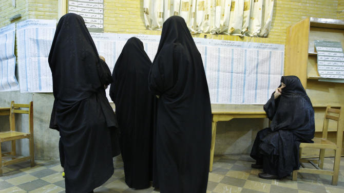 Head-to-toe veiled Iranian women attend a polling station to vote for the presidential and municipal councils elections in Tehran, Iran, Friday, June 14, 2013. What Iran's next president can potentially influence is the tone and tactics with world powers if stalemated nuclear talks resume at some point after a successor is picked for the firebrand President Mahmoud Ahmadinejad. (AP Photo/Vahid Salemi)