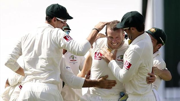 Teammates congratulate Australia's Peter Siddle (C) after he bowled South Africa's Alviro Petersen