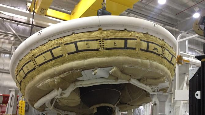 In this undated image provided by NASA a saucer-shaped test vehicle holding equipment for landing large payloads on Mars is shown in the Missile Assembly Building at the US Navy's Pacific Missile Range Facility in Kauai, Hawaii. On Wednesday, June 11, 2014 weather permitting, a balloon carrying the saucer-shaped vehicle is set to launch from Hawaii. (AP Photo/NASA)