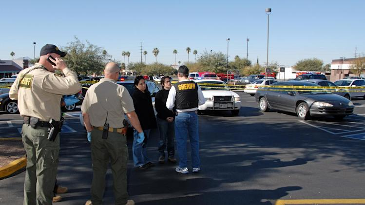 In this image released by the Pima County Sheriff's department, officers are seen speaking to people in the aftermath of the Tucson shooting rampage that killed six people and wounded former U.S. Rep. Gabrielle Giffords and 12 others in January 2011.  Authorities released more than 300 photos on Tuesday, May 21, 2013, made by investigators during their investigation in the parking lot of the shopping center where the shooting took place.  (AP Photo/Pima County Sheriff)