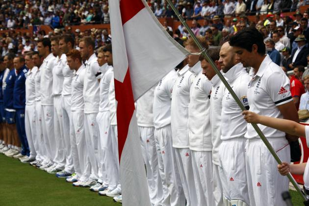England's captain Cook and his team stand as they observe a minute of silence to commemorate former South African President Mandela's death before starting second day's play in second Ashe