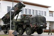 <p>A soldier from the Air Defence Missile Squadron 2 walks past a Patriot missile launcher in Bad Suelze, northern Germany. NATO on Tuesday agreed to deploy Patriot missiles along the border of member state Turkey as requested by Ankara to help it defend its territory against threats from Syria.</p>