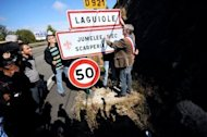 French chef Michel Bras (L) and local mayor, Vincent Alazard (R), remove a road sign reading the village name on September 19. Residents of Laguiole, a village synonymous with the manufacture of France's most famous knives, have symbolically 'unnamed' the place in protest at losing control of the name