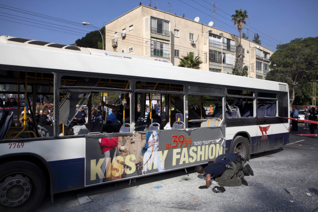 Israeli police officers examine a bus at the site of a bombing in Tel Aviv, Israel, Wednesday, Nov. 21, 2012. A bomb ripped through an Israeli bus near the nation's military headquarters in Tel Aviv o