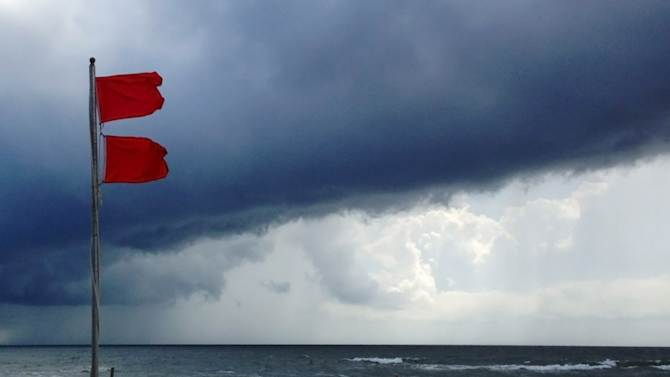Red flags warn swimmers to stay out of the Gulf of Mexico as a squall from Tropical Storm Karen moves offshore at Gulf Shores, Ala., on Saturday, Oct. 5, 2013. The beaches remained open, but authorities said dangerous underwater rip currents made the waters too dangerous to enter. (AP Photo/Jay Reeves)