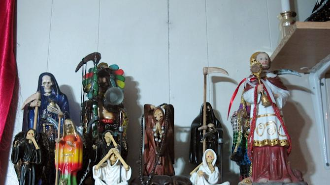In this Feb. 12, 2013 photo, statues of La Sante Muerte from an altar run by Arely Vazquez Gonzalez, a Mexican immigrant and transgender woman, is shown inside a Queens, NY apartment.  La Santa Muerte, an underworld saint most recently associated with the violent drug trade in Mexico, now is spreading throughout the U.S. among a new group of followers ranging from immigrant small business owners to artists and gay activists. (AP Photo/Russell Contreras)