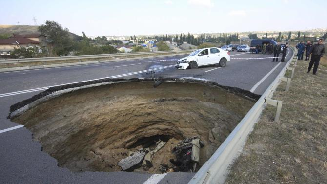 A car lies in a sinkhole in the road outside the Crimean capital Simferopol