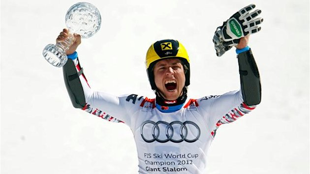 Austria's Marcel Hirscher celebrates with a trophy of the alpine ski men's World Cup Giant Slalom discipline at the World Cup finals in Schladming March 17, 2012