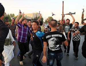 Shiite tribal fighters raise their weapons and chant…