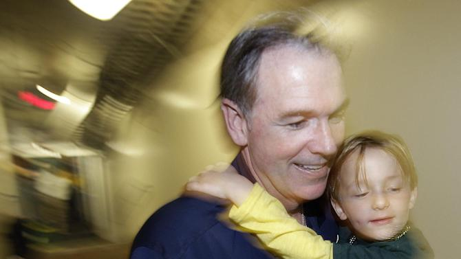 Oakland Athletics general manager Billy Beane carries a child as he heads to the clubhouse after the A's clinched the AL West title when they defeated the Texas Rangers 12-5 in a baseball game, Wednesday, Oct. 3, 2012, in Oakland, Calif. (AP Photo/Ben Margot)
