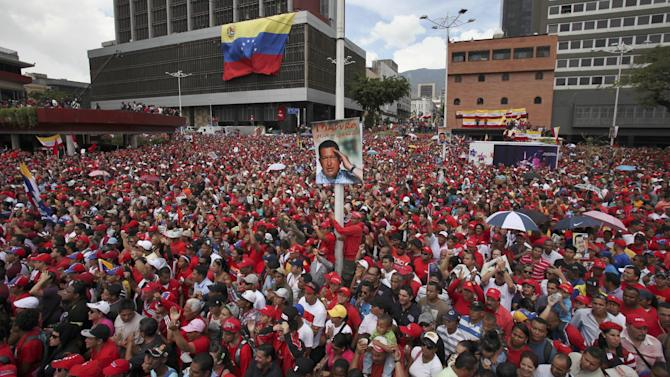 """Supporters of acting President Nicolas Maduro gather outside the national electoral council as he registers his candidacy to replace Chavez at the national electoral council in Caracas, Venezuela, Monday, March 11, 2013.  The poster on the post shows Chavez and reads in Spanish """"Maduro from my heart."""" Presidential elections were announced to take place on April 14, after Maduro announced on March 5 that Chavez had died. (AP Photo/Fernando Llano)"""