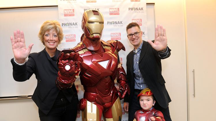 IMAGE DISTRIBUTED FOR PHONAK - Kimberly Rawn, left, of Phonak, and Bill Rosemann, right, of Marvel Custom Solutions, join Phonak hearing aid wearer Anthony Smith, 5, of Salem, NH, and Marvel's Iron Man, Tuesday, Feb. 26, 2013, in New York, to announce a unique partnership between Phonak and Marvel Custom Solutions to produce an educational poster geared for children that highlights the benefits of hearing aids. (Photo by Diane Bondareff/Invision for Phonak/AP Images)