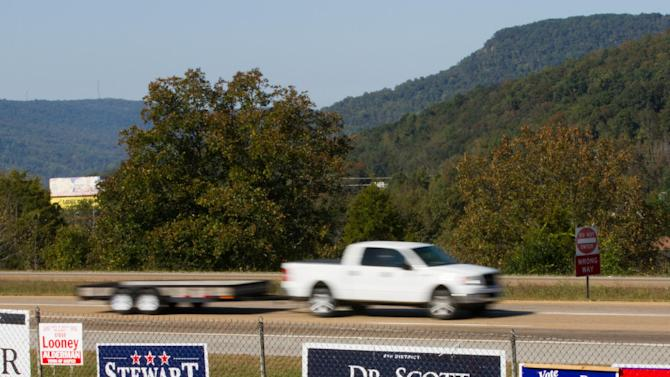 A truck drives by campaign signs for Republican U.S. Rep. Scott DesJarlais and his Democratic opponent Eric Stewart near Jasper, Tenn., on Thursday, Oct. 11, 2012. The Tennessee Republican Party issued a statement supporting DesJarlais despite the emergence of a transcript indicating he pressed a mistress to get an abortion more than a decade ago. (AP Photo/Erik Schelzig)