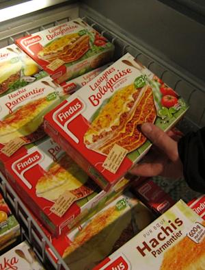 """A customer holds a pack of Findus Beef Lasagne Bolognaise in a freezer of a supermarket in Nice, southeastern France, Monday, Feb. 11, 2013. Complex trading between wholesalers has made it increasingly difficult to trace the origins or destination of food like the horsemeat disguised as beef being sold in frozen meals across Europe's open borders, and France's agricultural minister said it was up to regulators to find a way """"out of the fog."""" (AP Photo/Lionel Cironneau)"""