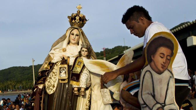 People carry a statue of the Virgin of Carmen during a procession at the dock of San Juan del Sur, Nicaragua, Tuesday, July 16, 2013. Nicaragua's fishing community celebrate the feast day of the Virgin Carmen who is worshipped by Catholics as the patron saint of fishermen and sailors. (AP Photo/Esteban Felix)