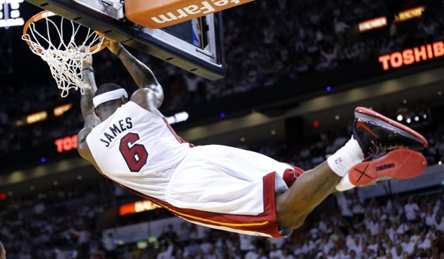 Miami Heat's LeBron James hangs on the rim after slam dunking against the Indiana Pacers during Game 2 of their NBA Eastern Conference final basketball playoff in Miami