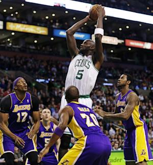 Boston Celtics forward Kevin Garnett (5) shoots while surrounded by Los Angeles Lakers during the first half of an NBA basketball game in Boston, Thursday, Feb. 7, 2013. (AP Photo/Charles Krupa)