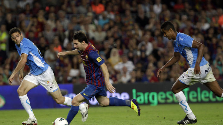 FC Barcelona's Lionel Messi from Argentina, center, duels for the ball for scores next to Osasuna's Roversio Rodrigues de Barros from Brazil and Dami Abella during a Spanish La Liga soccer match at the Camp Nou stadium in Barcelona, Spain, Saturday, Sept. 17, 2011. (AP Photo/Emilio Morenatti)