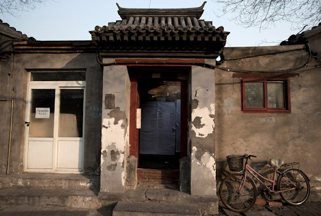 Associated Press/Andy Wong - In this photo taken on Dec. 26, 2012, a bicycle is parked outside a Hutong home with a demolition notice seen behind the entrance wall near the historical Drum and Bell Tower in Beijing. The district government wants to demolish these dwellings, move their occupants to bigger apartments farther from the city center and redevelop a square in 18th century Qing Dynasty fashion. (AP Photo/Andy Wong)