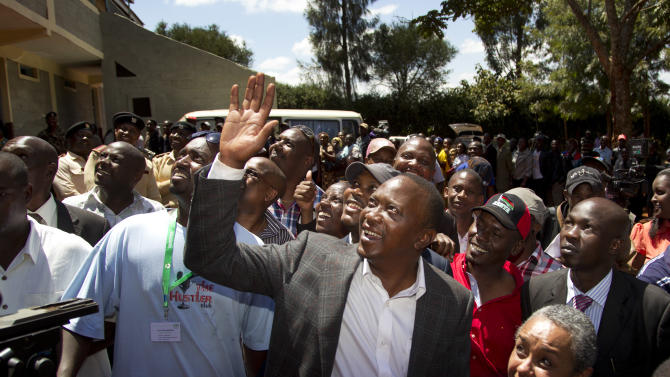 Kenyan Presidential candidate Uhuru Kenyatta waves to queuing voters after casting his vote, accompanied by his wife Margaret Wanjiru Gakuo, below right, at the Mutomo primary school near Gatundu, north of Nairobi, in Kenya Monday, March 4, 2013. Five years after more than 1,000 people were killed in election-related violence, Kenyans went to the polls on Monday to begin casting votes in a nationwide election seen as the country's most important - and complicated - in its 50-year history. (AP Photo/Ben Curtis)
