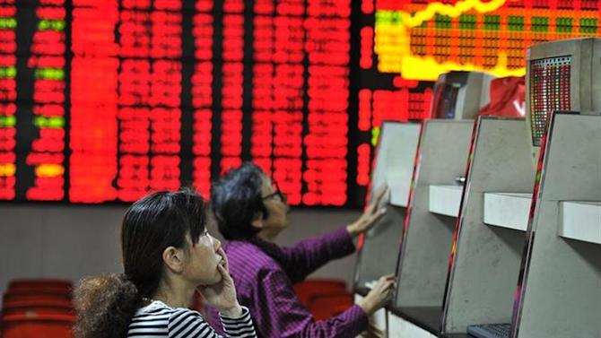 Investors look at computer screens in front of an electronic board showing stock information at a brokerage house in Hefei, Anhui province October 8, 2013. REUTERS/Stringer