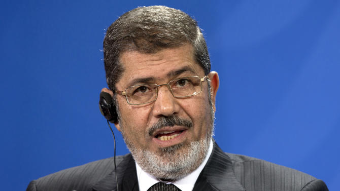 """FILE - In this Wednesday, Jan. 30, 2013 file photo, the President of Egypt, Mohammed Morsi, addresses the media during a joint press conference with German Chancellor Angela Merkel, unseen, after a meeting at the chancellery in Berlin, Germany, Wednesday.  Morsi, in a rambling 2.15-hour TV interview that aired in the early hours of Monday, Feb, 25, 2013, dismissed the masses protesting against his rule across much of the nation as """"thugs"""" and """"outlaws."""" (AP Photo/Michael Sohn, File)"""
