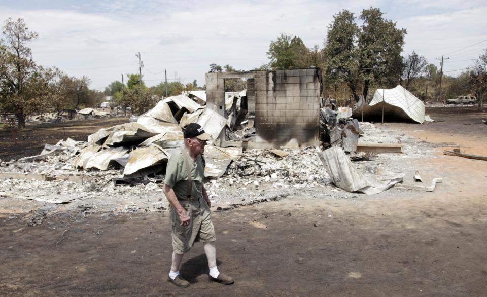 Bill Ragle walks past the remains of his home that was destroyed by a wildfire in Mannford, Okla., Sunday Aug. 5, 2012. (AP Photo/Tulsa World Mike Simons)