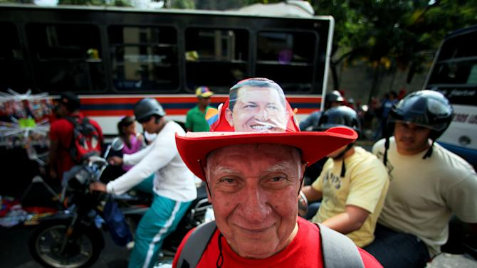 A supporter of Venezuela's President Hugo Chavez wears a hat decorated with his picture at a rally in Caracas, Venezuela, Wednesday, Jan. 23, 2013. The cult of personality that Chavez long nurtured has been flourishing like never before as his supporters' devotion has intensified into a fervor that borders on deification. (AP Photo/Fernando Llano)