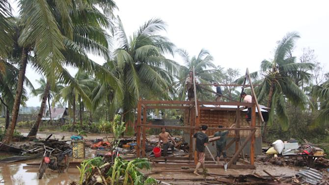 Residents repair their damaged homes after Typhoon Bopha made landfall in Compostela Valley in southeastern Philippines Tuesday Dec. 4, 2012. Typhoon Bopha (local name Pablo), one of the strongest typhoons to hit the Philippines this year, barreled across the country's south on Tuesday, killing at least 40 people and forcing more than 50,000 to flee from inundated villages.  (AP Photo/Karlos Manlupig)