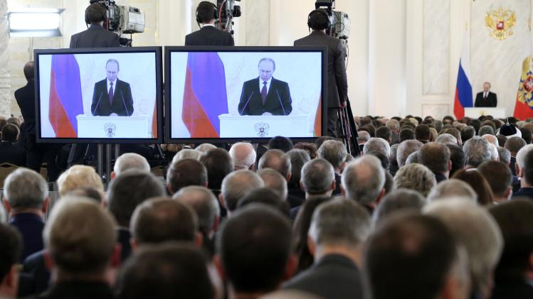 The audience listen to Russia's President Putin during his annual state of the nation address at the Kremlin in Moscow