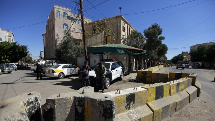 Yemeni security personnel stand behind concrete barriers at the entrance of the German embassy in Sanaa