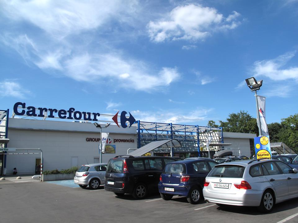 This picture taken Aug. 13, 2011 shows the  Carrefour supermarket  in Ferney-Voltaire, France  where Swiss license plates are prevalent in the parking lot just over the border from Geneva. The Swiss are taking advantage of the strong franc to buy in the Eurozone.  (AP Photo/John Heilprin)