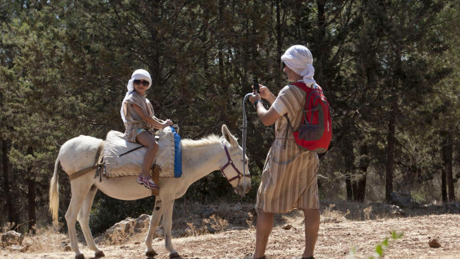 American tourist Peter Scherr uses a smartphone to send a photograph of his daughter using a Wi-Fi router placed on a donkey Kfar Kedem, a biblical reenactment park in the village of Hoshaya in the Galilee, northern Israel, Wednesday, Aug. 22, 2012. Visitors riding donkeys through the Old Testament landscape can now also surf the web while being transported across the land of the Bible. Organizers are hoping to connect the younger generation to ancient Galillee life while allowing them to like, share, tweet and snap it instantly to their friends. (AP Photo/Ariel Schalit)