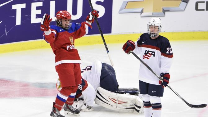 Russia's Lyudmila Belyakova, left, celebrate after scoring past U.S. goalkeeper Molly Schaus, center, as Michelle Picard, looks on during the 2015 Women's Hockey World Championship group A match between Russia and USA, at Malmo Isstadion in Malmo, southern Sweden, Tuesday, March 31, 2015.  (AP Photo/TT, Claudio Bresciani) SWEDEN OUT