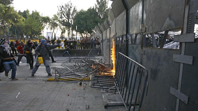 CORRECTS DAY OF THE WEEK TO SATURDAY .-  Protestors clash with police outside the steel security barriers around the National Congress, where the swearing in of new Mexican President Enrique Pena Nieto will take place in Mexico City, Saturday Dec. 1, 2012.  Pena Nieto took power at midnight in a symbolic ceremony and will formally take the oath of office Saturday morning after campaigning as the face of a new PRI _ a party that claims to be repentant and reconstructed after voted out of the presidency in 2000.(AP Photo / Marco Ugarte)
