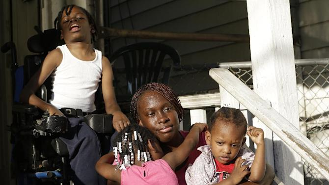 In a Wednesday, Oct. 2, 2013 photo, Patricia Jones, 34, center, is hugged by her 4-year-old daughter Pashalae Armstrong, 4, center left, while talking to The Associated Press outside of her home in Newark, N.J., with her other children, Nature Harris, 15, top, and Latrell Armstrong, 2, right. Jones was denied getting a proof printout of Harris' disability to apply for government aid because the shutdown has closed her local social security office. Like millions of other low-income women, Jones relies on the federal Women, Infants and Children program to pay for infant formula _ a program that's now jeopardized by the federal government shutdown. New Jersey and other states say they have enough money to operate the program for another few weeks, but advocates worry what will happen next. (AP Photo/Julio Cortez) Jones was denied getting a proof printout of Harris' disability to apply for government aid because the shutdown has closed her local social security office. Like millions of other low-income women, Jones relies on the federal Women, Infants and Children program to pay for infant formula _ a program that's now jeopardized by the federal government shutdown. New Jersey and other states say they have enough money to operate the program for another few weeks, but advocates worry what will happen next. (AP Photo/Julio Cortez)