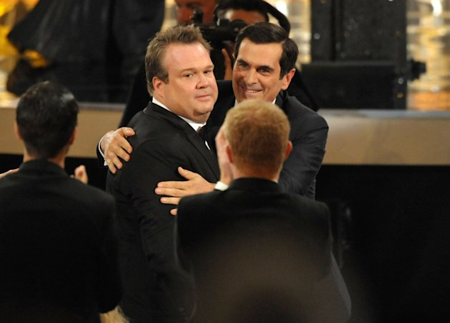 "Ty Burrell, right, congratulates Eric Stonestreet after Stonestreet won the award for outstanding supporting actor in a comedy series for ""Modern Family"" at the 64th Primetime Emmy Awards at the Nokia Theatre on Sunday, Sept. 23, 2012, in Los Angeles. (Photo by John Shearer/Invision/AP)"