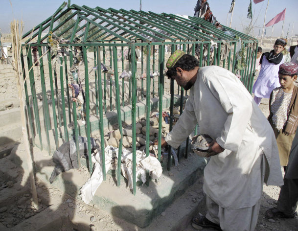 An Afghan man collects victims&#39; belongings at the scene of an explosion at a cemetery in Lashkar Gah, southwest of Kabul, Afghanistan, Sunday, Aug. 19, 2012. A bomb hidden in the cemetery exploded Sunday as a police official and his family were visiting the grave of a relative, killing the official and his brother, police said. (AP Photo/Abdul Khaleq)