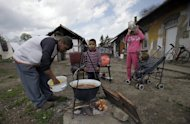 A man prepares lunch with his children at their home in Miskolc, Hungary on April 22, 2012. EU statistics show a poverty rate of 13% in Hungary, but the figure falls far short of revealing the depths of desperation plaguing some communities