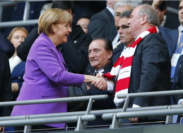 File photo of German Chancellor Merkel shakes hands with Bayern Munich President Hoeness before Champions League final in London