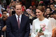 Britain's Prince William and his wife Catherine, the Duchess of Cambridge, walk in the gardens of the KLCC in Kuala Lumpur on September 14. A French magazine has said it will publish topless pictures of Kate on Friday, in a move met with dismay by the royal couple