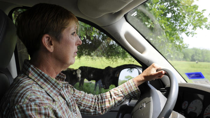 Rancher Linda Galayda cruises around a pasture checking on her cattle Friday, April 27, 2012, at her ranch in Elkhart, Texas. (AP Photo/Pat Sullivan)