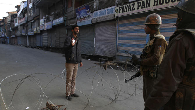 Indian paramilitary soldiers interrogate a civilian near a barbed wire set up as road blockade during curfew in Srinagar, India, Saturday, Feb. 9, 2013. A Kashmiri man Mohammed Afzal Guru, convicted in the 2001 attack on India's Parliament, has been hanged in an Indian prison, a senior Indian Home Ministry official said Saturday. On Saturday morning thousands of police and paramilitary troops had fanned out across Indian Kashmir anticipating that protests and violence might follow news of the execution. (AP Photo/Mukhtar Khan)