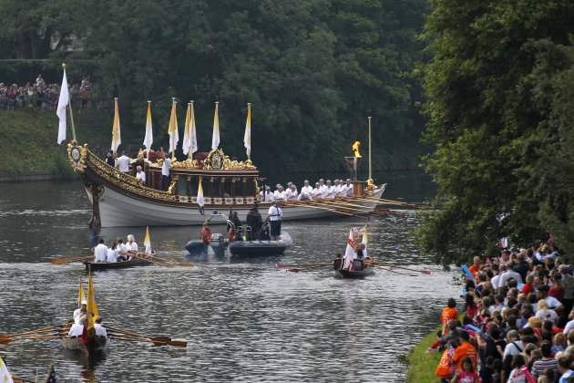 The royal barge Gloriana carries the Olympic flame in a cauldron on board, as it leaves Hampton Court Palace in London, as it makes its way along the river Thames into central London on the final day of the Torch Relay, Friday, July 27, 2012. (AP Photo/Sang Tan)