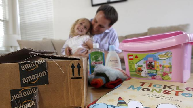 Reid Butler plays with his daughter Siena, 2, as they pose for photographs with recent online purchases from Amazon at their home in Walnut Creek, Calif., Thursday, Sept. 13, 2012. Products are flying off the shelves at Amazon warehouses across the county as Californians prepare to start paying sales taxes on online purchases. (AP Photo/Jeff Chiu)