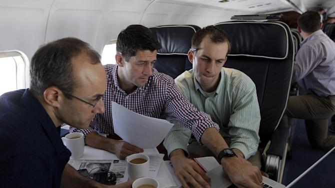 Republican vice presidential candidate, Rep. Paul Ryan, center,  R-Wis., works on the speech he will deliver at the Republican National Convention, with senior adviser Dan Senor, left, and senior aid Conor Sweeney. during the campaign charter flight from Wisconsin to Tampa, Tuesday, Aug. 28, 2012.  (AP Photo/Mary Altaffer)