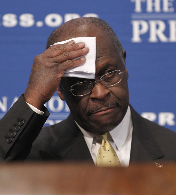 Republican presidential candidate, Herman Cain wipes his forehead before answering questions at the National Press Club in Washington, Monday, Oct., 31, 2011. Denying he sexually harassed anyone, Cain