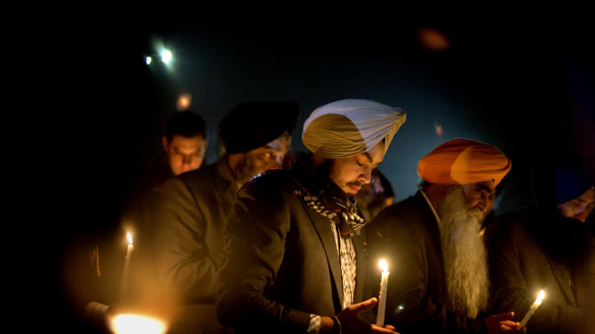Varinder Singh, of the Queens borough of New York, joins a group of Sikhs from around the Northeastern U.S., in a moment of prayer as a memorial service is broadcast over a loudspeaker outside Newtown High School for the victims of the Sandy Hook Elementary School shooting, Sunday, Dec. 16, 2012, in Newtown, Conn. (AP Photo/David Goldman)