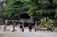 <p>A Myanmar policeman patrols the streets of Sittwe, capital of Myanmar's western state of Rakhine in June 2012. Ongoing fighting in northern Kachin state has displaced tens of thousands of people and cast a shadow over the nationwide peace efforts.</p>
