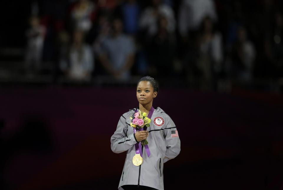 U.S. gymnast and gold medallist  Gabrielle Douglas stands for her national anthem during the artistic gymnastics women's individual all-around competition at the 2012 Summer Olympics, Thursday, Aug. 2, 2012, in London. (AP Photo/Gregory Bull)